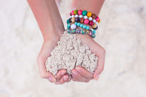 Woman scooping sand and wearing colorful bracelets.