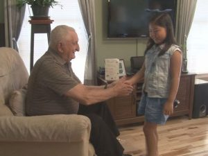 Young girl greets veteran.