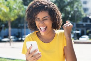 Young woman winning online auction on mobile phone.