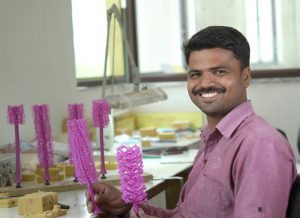 Worker displays a wax tree for jewelry molding.