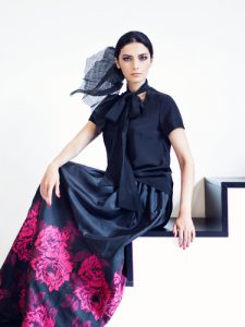 Woman in floral pattern skirt with solid black top.
