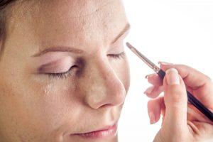 Woman applying eyeshadow primer