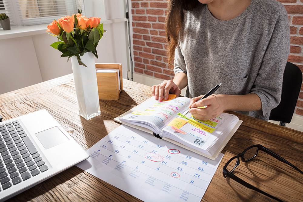 Woman in office planning with a planner.