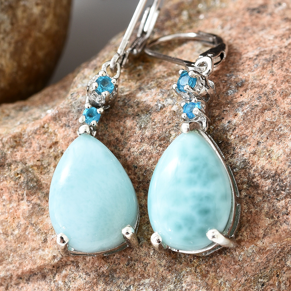 Closeup of larimar earrings against marble background