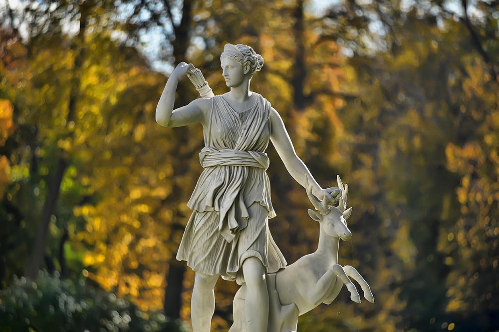 Artemis statue against green trees.