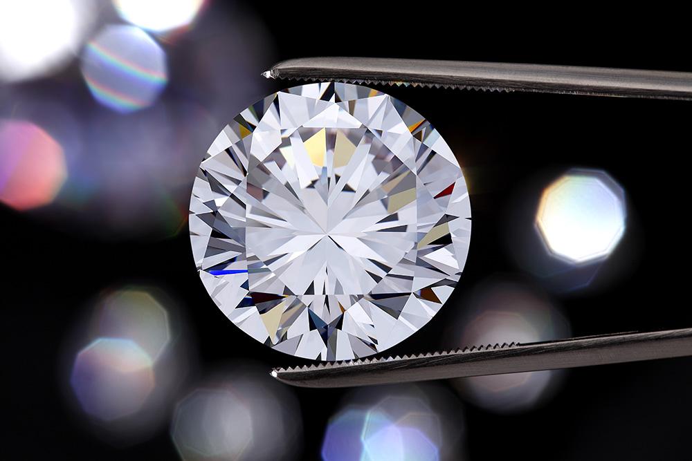 Closeup of diamond held with tweezers.