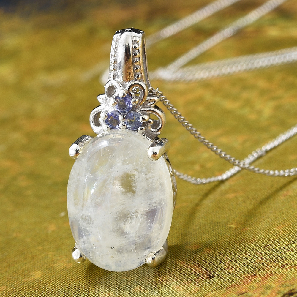 Closeup of moonstone necklace against yellow-green background.