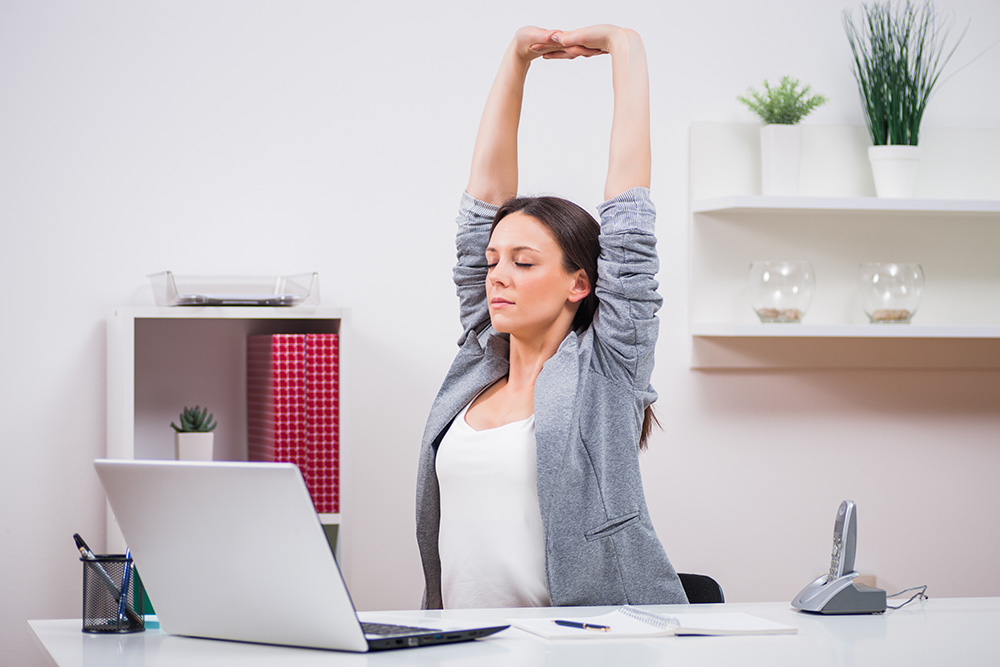 Business woman stretching at her desk.