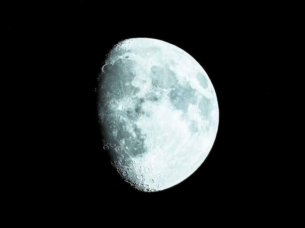Closeup of Waxing moon against starless black space.