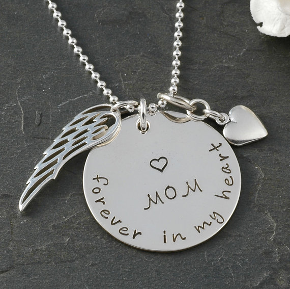 Closeup of silver necklace with engraved writing honoring a mother.