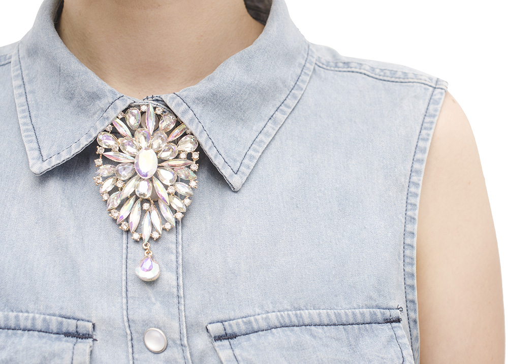 Closeup of faux necklace on denim top