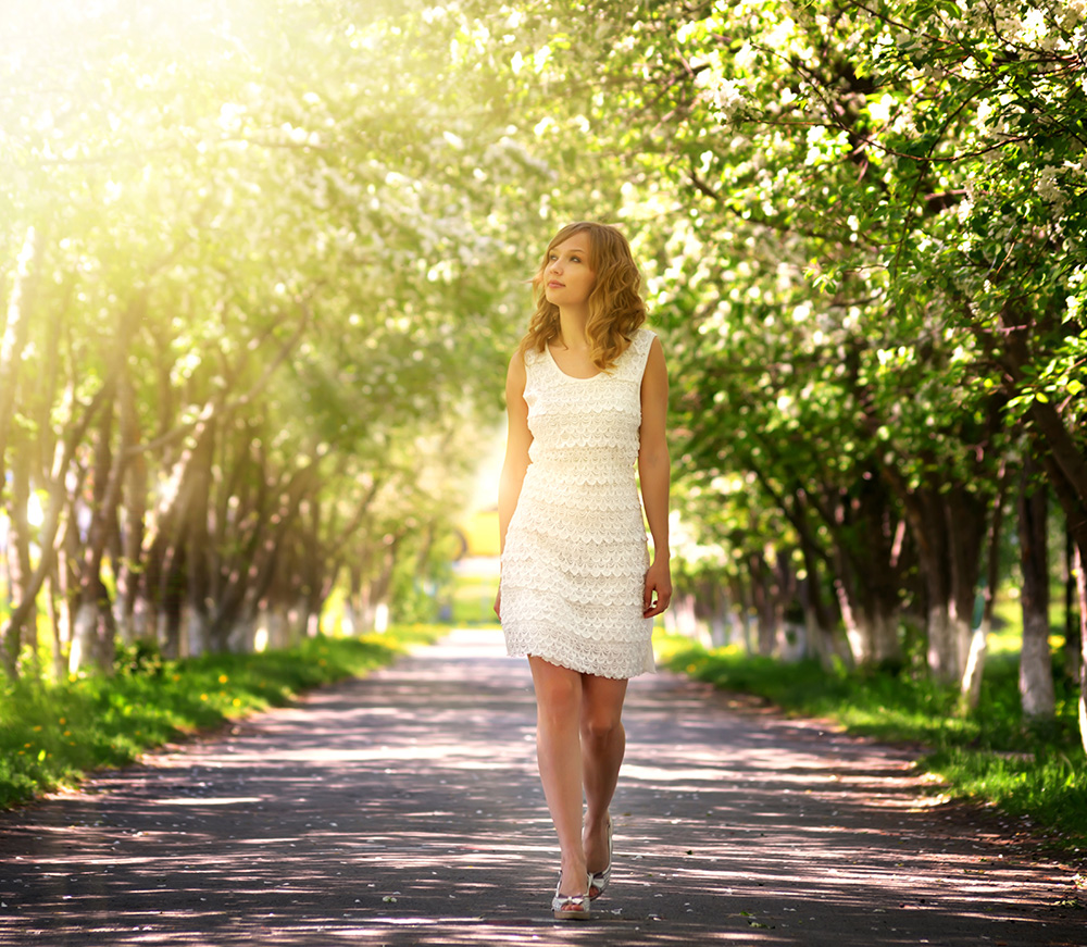 Woman in white dress walking in nature.