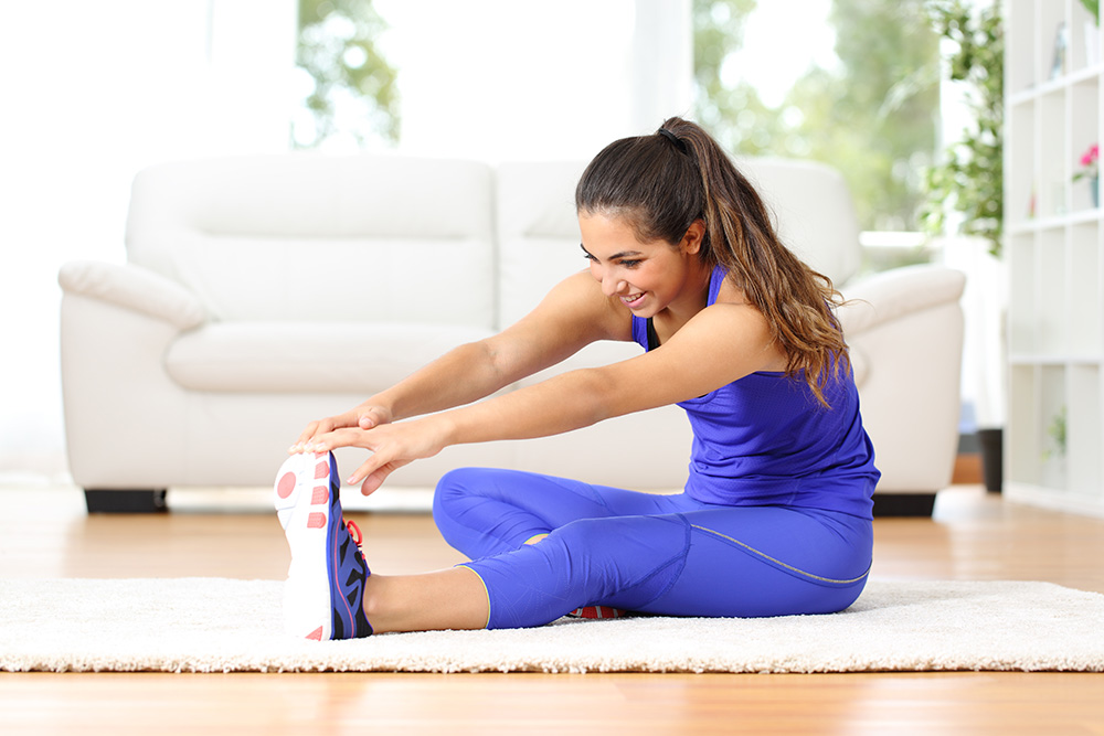 Woman in blue workout gear stretching in her living room.