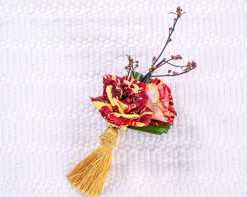 Closeup of flower and yellow tassel brooch