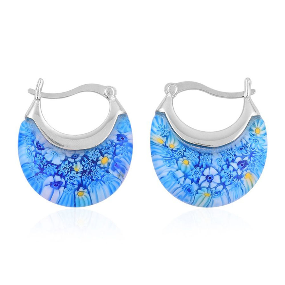 Closeup of blue earrings against white background