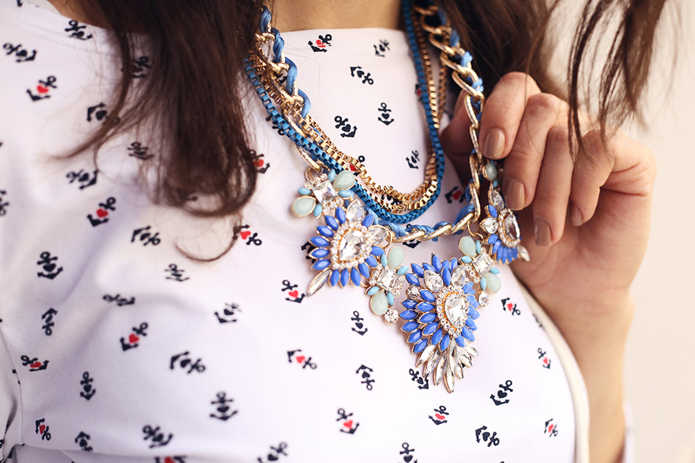 Closeup of woman wearing layered necklace