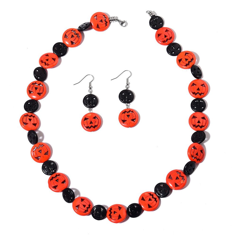 Closeup of orange pumpkin and black beads necklace and drop earrings against white background
