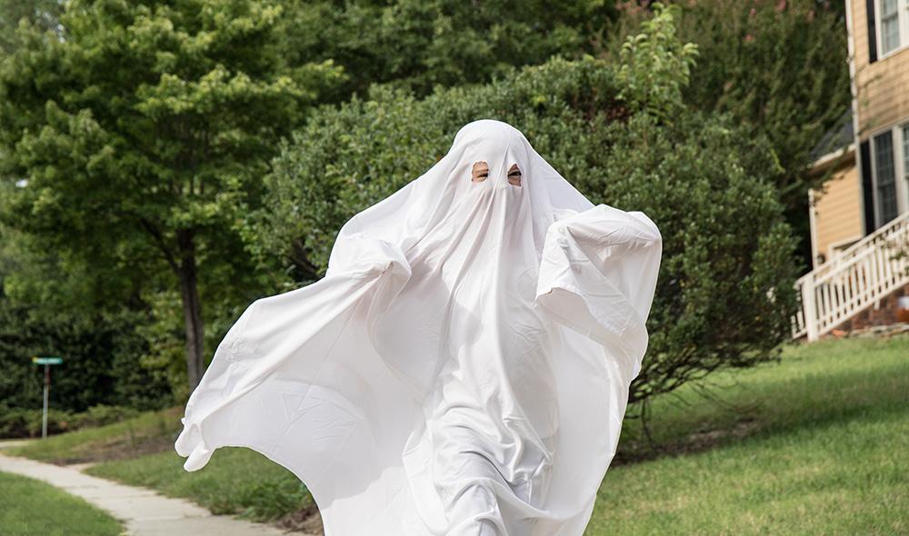 Kid running down the neighborhood dressed as a ghost