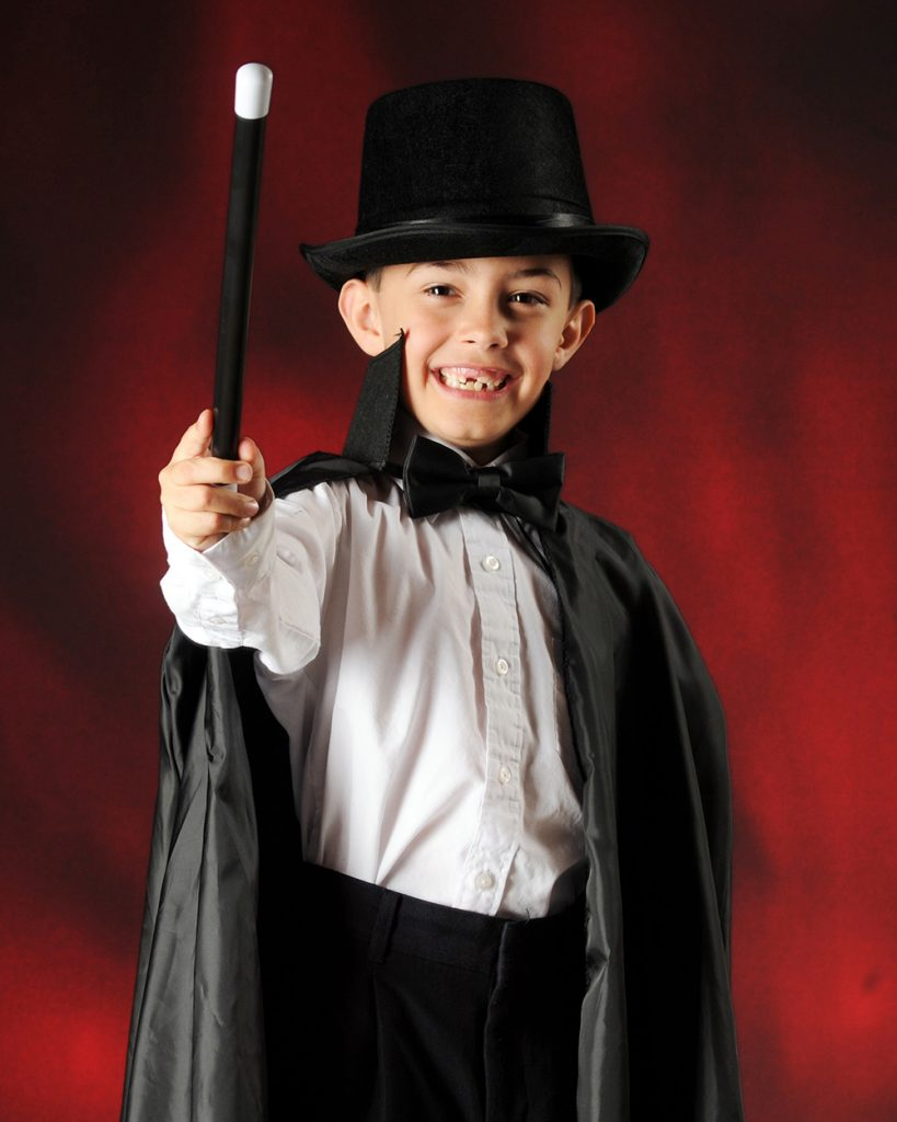 Kid dressed as a magician in front of red curtain