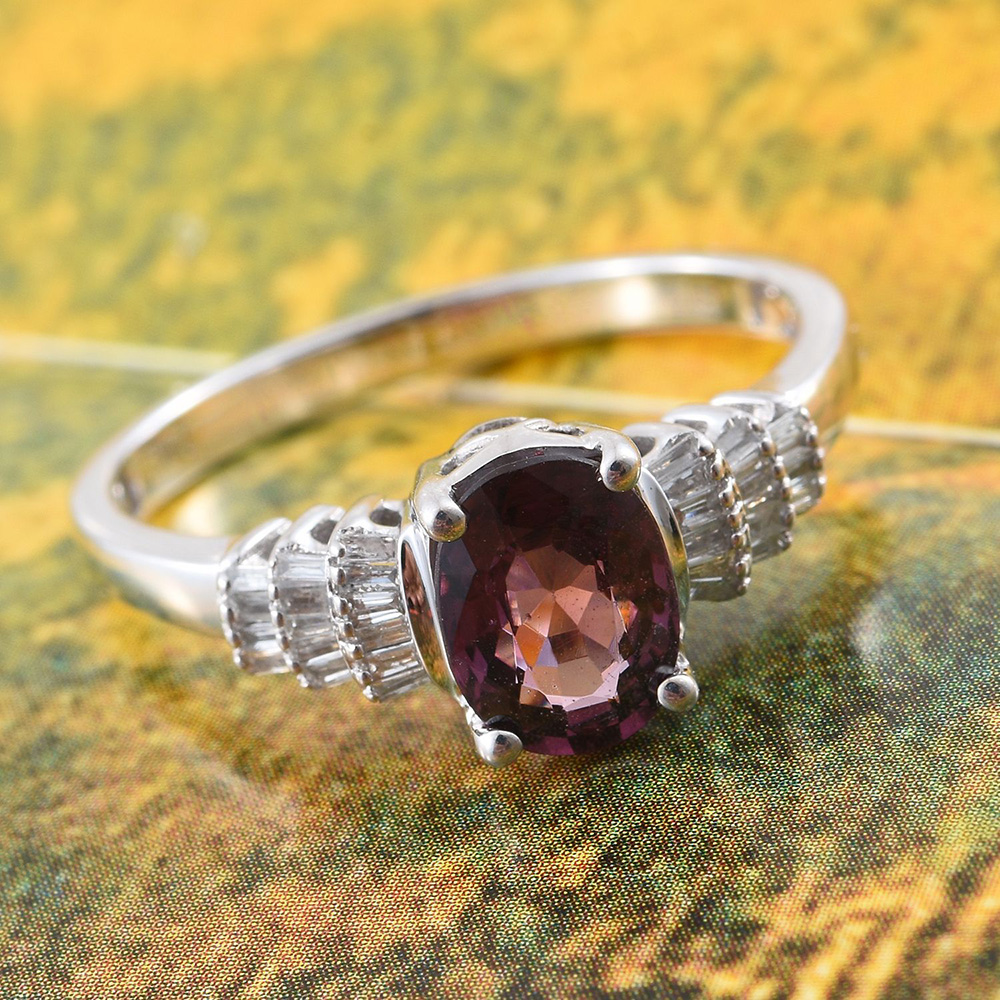 Closeup of red spinel ring against yellow and green background