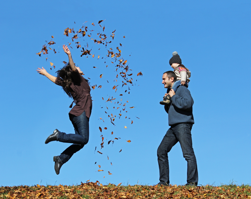 Woman jumping with joy and throwing leaves around her family