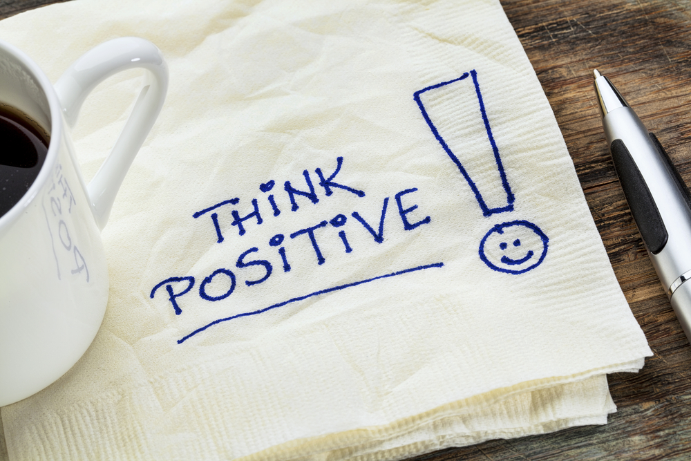 """Written """"Think Positive"""" on a napkin by a coffee cup"""