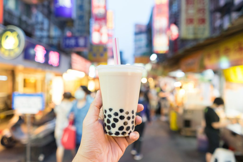 Hand holding up a cup of refreshing boba tea on busy street.