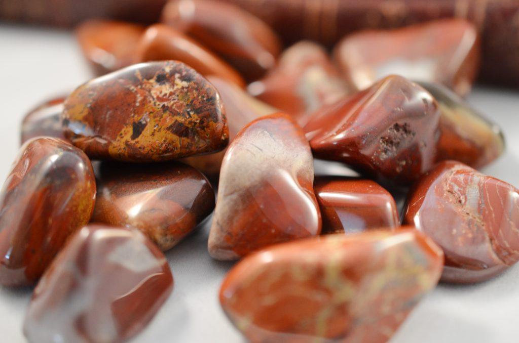 Tumbled brownish orange jasper stones.