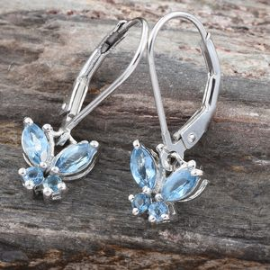 Aquamarine butterfly earrings on wood background.