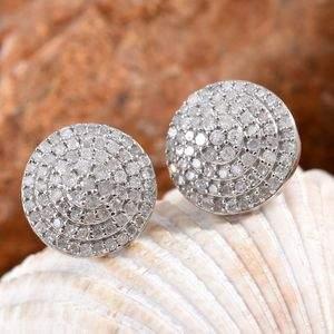 Diamond cluster earrings resting on shell.