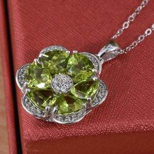 Peridot floral pendant resting on top of red silk box.