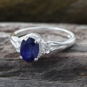 Blue sapphire ring in silver against wood platform.
