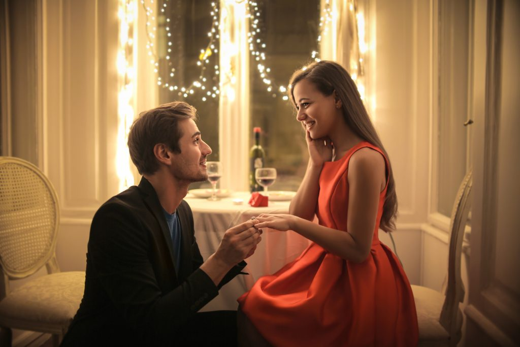 Man proposing to woman during candlelit dinner.