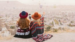 Women wearing Southwestern-inspired clothing watching hot air balloons.