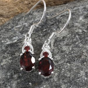 Mozambique garnet earrings against granite backdrop.