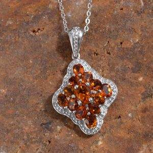 Citrine cluster pendant draped over red granite display board.