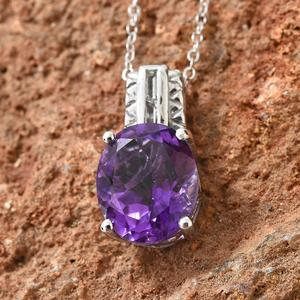 Amethyst pendant displayed against red stone.