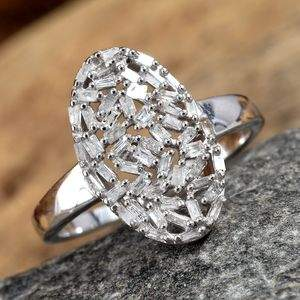 Oval diamond cluster ring resting on granite stone.