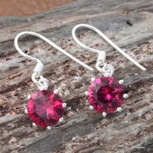 Lab created ruby drop earrings draped over wooden display.