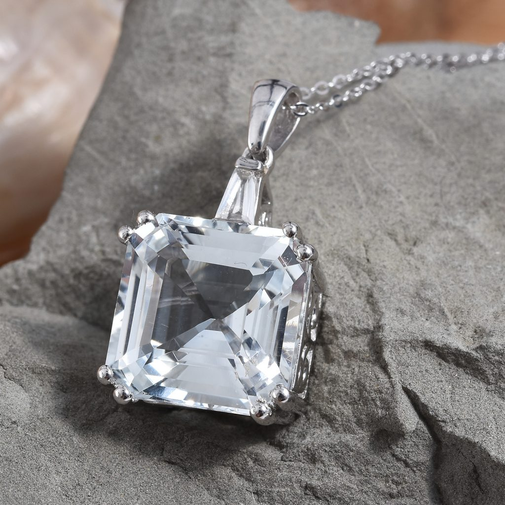 Asscher cut pendant necklace on slate background.