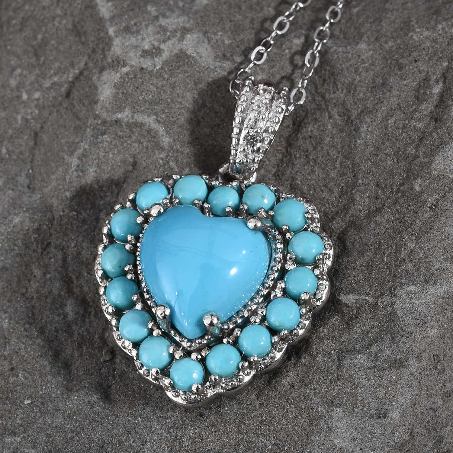 Turquoise heart pendant draped over slate-colored stone.