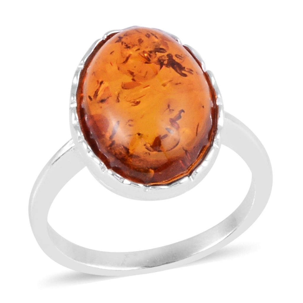 Amber solitaire ring in sterling silver on white background.