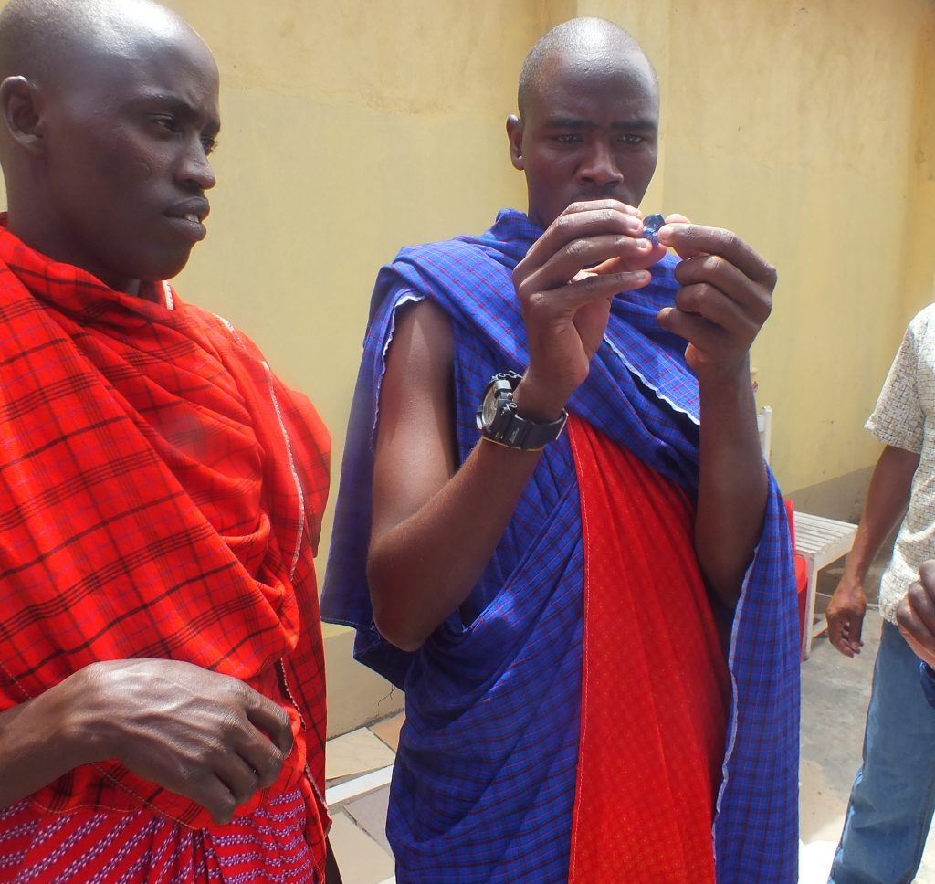 Young Maasai man examines tanzanite.