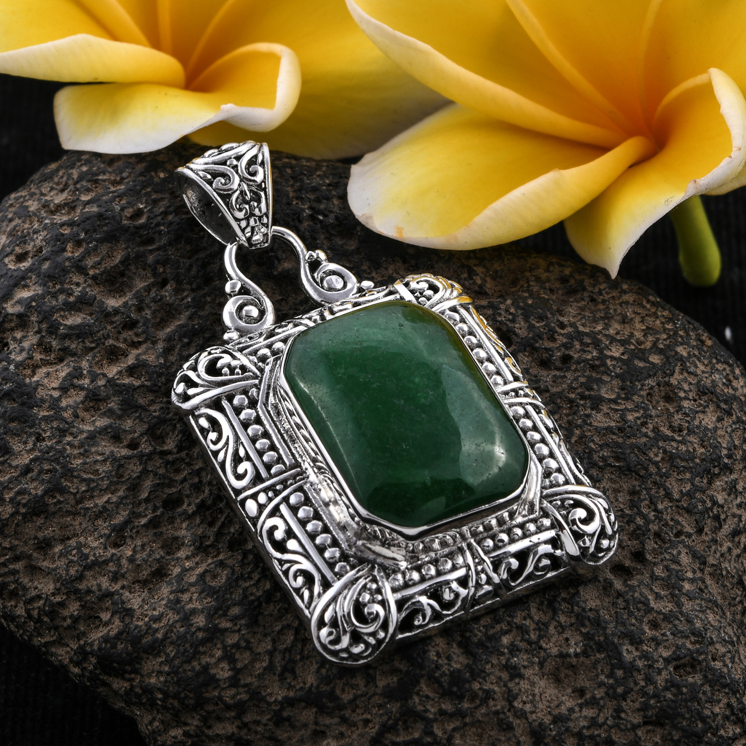 Bali crafted jade pendant on gray stone.