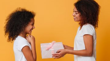Sisters exchanging gifts against orange background