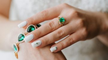 Closeup of woman wearing emerald ring and emerald bracelet