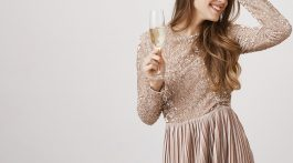 Woman smiling holding champagne glass wearing champagne colored dress