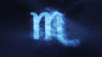 Scorpio sign in front of navy blue background