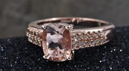 Morganite ring in rose gold on black sand.