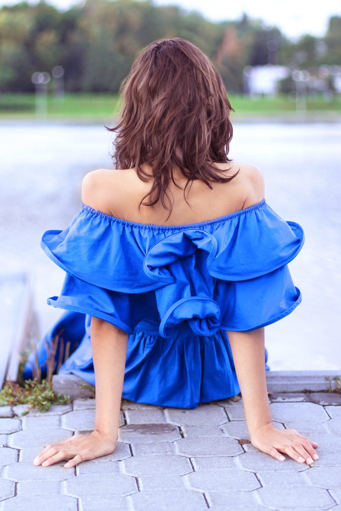 Woman wearing blue dress and sitting on steps.